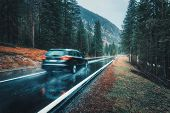 Blurred Car In Motion On The Road In Autumn Forest In Rain poster
