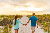 Happy young couple in love walking on romantic evening beach stroll at sunset. Lovers holding hands  poster