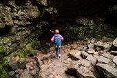 Woman Traveler Explore Lava Tunnel In Iceland. poster