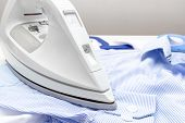 White Modern Electrical Iron Close Up And Blue Shirts On The Table - Ironing, Laundry And Housework  poster