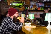 Man With Beard Eat Burger Menu. Brutal Hipster Bearded Man Sit At Bar Counter. High Calorie Food. Ch poster