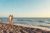 Happy Romantic Middle Aged Couple Enjoying Beautiful Sunset Walk On The Beach. Travel Vacation Retir poster