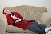 stock photo of housecoat  - A young man laying on a sofa in his bathrobe feeling ill because he has the flu - JPG