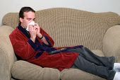 pic of housecoat  - A sick man lying on a couch blowing his nose - JPG