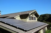 Solar Panels On Roof Of House. Horizontal Orientation, Blue Sky, Gray Panels On Brown Roof. poster