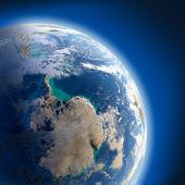 stock photo of planet earth  - A fragment of the Earth with high relief detailed surface translucent ocean and atmosphere illuminated by sunlight - JPG
