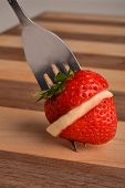 Strawberry and Slice of Banana on cutting board with fork