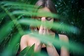 Portrait Of Cute Young Woman Meditating And Doing Namaste Hand In Jungle. Sunny Day poster