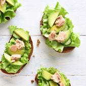 Tuna Sandwiches With Avocado And Lettuce Leaves Over Light Wooden Background. Tasty Tuna Sandwiches  poster