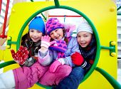 Happy kids in winterwear looking at camera while having fun on playground