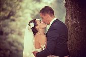 stock photo of white gown  - Wedding shot of bride and groom in park - JPG