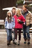 Teenage Family Walking Along Snowy Town Street In Ski Resort