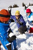 Family Having Snowball Fight On Ski Holiday In Mountains