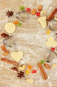 Frame made of candied fruit, nuts, unbaked biscuits and molds for cookies on a wooden table close-up