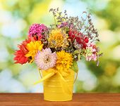 Bright yellow bucket with flowers on green background