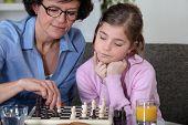 Girl and her grandmother playing chess
