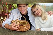 young couple behind a wooden barrier in autumn, the man is holding a wickerwork basket containing mushrooms and chestnuts