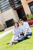 Couple looking very happy sitting in their frontyard