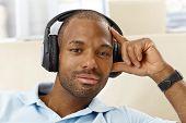 Retrato de homem étnico bonito com fones de ouvido, olhando para a câmera, gostaria.