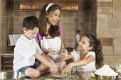 An attractive smiling family of mother, and two children, boy, girl, son, daughter baking and eating