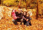 Picture of cheerful young family playing game in autumnal woods, portrait of cute kids with parents