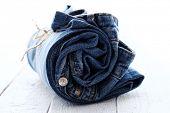 Close-up de jeans rolo sobre superfície de madeira