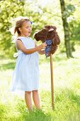 Young Girl Playing With Hobby Horse In Summer Field