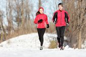Sport couple running in winter. Runners jogging in snow in city park. Interracial young happy couple