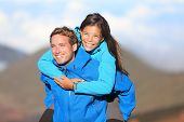 Happy hiking couple piggyback having fun on hike. Fresh young blissful interracial couple. Asian wom