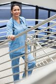 Smiling nurse in a stairwell leaned on the railings in hospital corridor