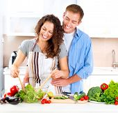 Happy Couple Cooking Together - Man and Woman in their Kitchen at home Preparing Vegetable Salad.Die