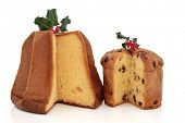 Panettone and pandoro christmas cakes with holly and red berry leaf sprig decoration over white background.