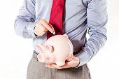 business man holding a pig bank - economy savings