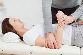 Physiotherapist manipulating the arm of a peaceful woman in a room