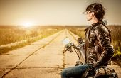 stock photo of motorcycle  - Biker girl sits on a motorcycle - JPG