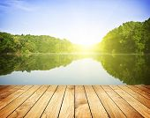 stock photo of leak  - Sunset on forest lake and wooden board background - JPG