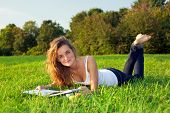 Beautiful ?oung Woman Reading On A Green Meadow