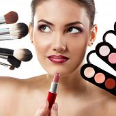 beauty portrait of young beautiful woman with makeup brushes, lipstick and palette of eye shadows is