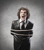 Businessman tied with a rope screaming