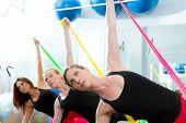 Grupo de mulheres de pilates aeróbica com faixas de borracha em uma linha no ginásio de fitness