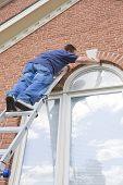 Painter Painting Trim Around Doors Windows