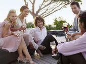 Grupo de amigos multiétnicas, beber y socializar en el porche