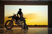 Uma menina e uma motocicleta no hangar.