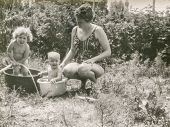 Vintage photo of woman washing two children in washtubs, eighties