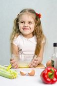 Girl playing in a cook churn whisk the eggs in a glass bowl
