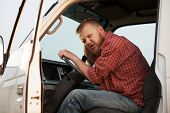 picture of stagnation  - Somewhat puzzled bearded driver in the cab of his truck - JPG