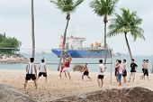 Group Of Men Play Volleyball On Beach