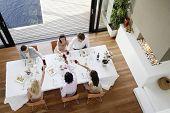 Vista de alto ángulo de amigos multiétnicas tostado vino a través de la mesa en la cena