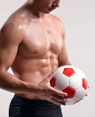 fitness and strong soccer player holding a soccer ball.