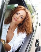 Beautiful middle-aged redhead woman behind steering wheel